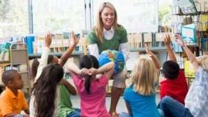 Kindergarten teacher and children with hands raised